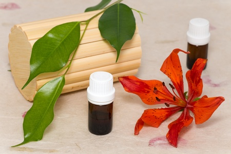 traquility: bottles of aromatic oil and lily flower Stock Photo