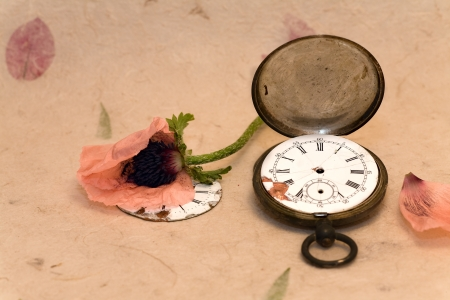 Old pocket watch and poppy on handmade paper with leaves photo