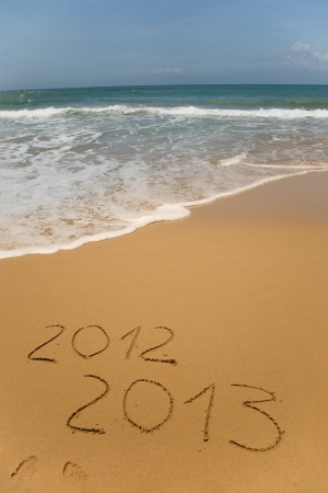 2012 and 2013 written in sand on beach with sea waves starting to erase the word  Banco de Imagens