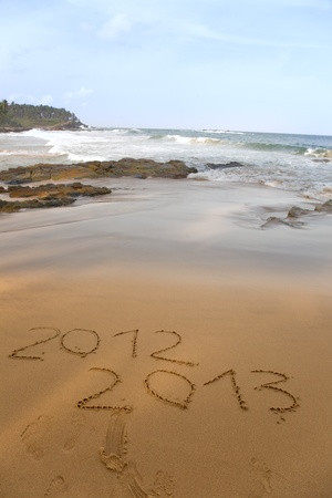 2012 and 2013 written in sand on beach with sea waves starting to erase the word  photo