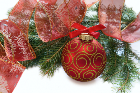 Christmas red ball, twig of fir , ribbon with drawing of tree ana star photo