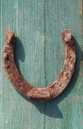 old rusty iron horseshoe on a wood background photo
