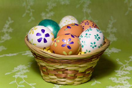 eastertime: Colored  easter eggs  with flower laying in wood basket