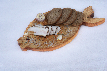 smoked lard with spice and different bread  on the board