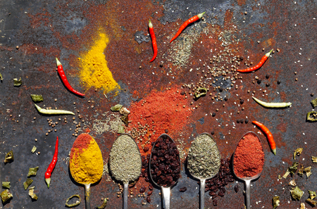 an assortment of different spices for cooking in silver spoon   . Red chilli peppers, Red Pepper Flakes, yellow turmeric, green rosemary on iron rustic background