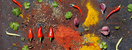 an assortment of different spices for cooking   . Red chilli peppers, Red Pepper Flakes, yellow turmeric, green rosemary on iron rustic background