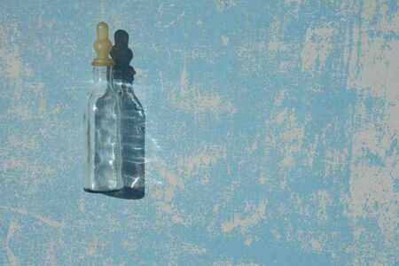 Empty transparent baby bottle for  feeding newborn babies with shadow  on  blue pastel colors  wooden  background under the natural light of the sun. Flat lay. Creative copyspace.