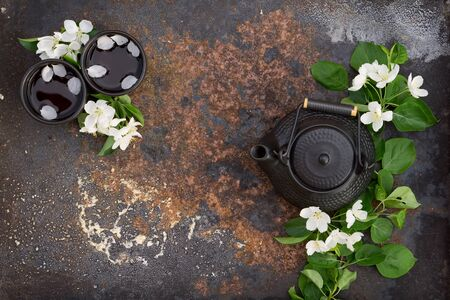 Black ceramic teapot and cup with hot tea decorated by spring blossom apple branches over dark texture  rustic iron background.  Flat lay spring tea consept