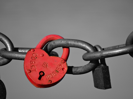 The lock in the form of a heart hangs on a steel chain. A photo Stok Fotoğraf