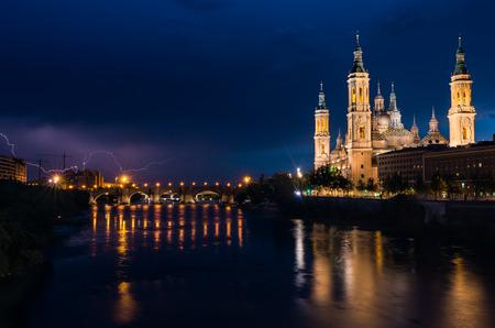 Basilica of Our Lady of the Pillar and Ebro River, Zaragoza, Aragon, Spain. Lighting storm Stock Photo