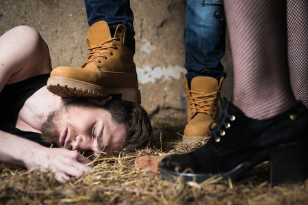Closeup of a mans foot crushing mans head. Homophobic people Stock Photo