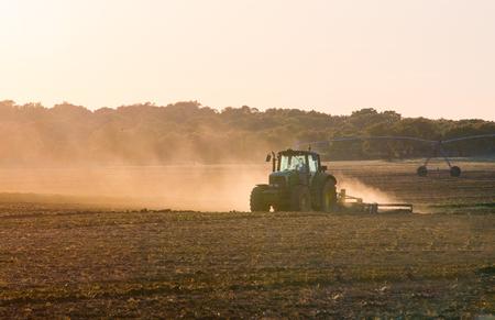 Tractor werkt op een boerderij in de schemering Stockfoto - 77148163