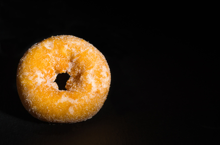 mini donuts sugar,sweet pieces of sugar doughnuts on black background, Copy space Imagens