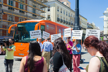 """homophobia: Madrid, Spain - june 06, 2017: Bus anti-transgender Hazte Oír (""""Make Yourself Heard"""").Bus   with the message written on the sides Boys have penises, girls have vulvas.Say no to gender indoctrination"""