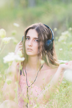 Beautiful Sexy Woman with Headphones listening music on Outdoors flowers field. Lifestyle portrait