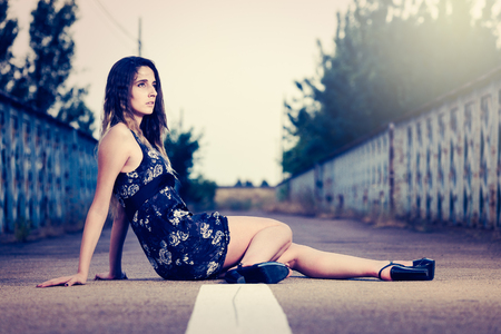 gloom: Dramatic portrait of a beautiful girl sitting in the middle of an empty road Stock Photo