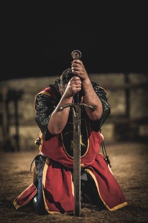 Middeleeuwse ridder knielt met zwaard na de strijd Redactioneel
