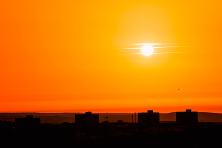 Photo of beautiful orange sunset on the city of Badajoz, silhouette city in sunrise on seashore, peaceful landscape, sun down on town on warm weather,  heat concept