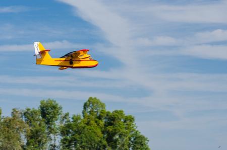 Radio controlled model hydroplane  flying on a nice cloudy day . Stock Photo