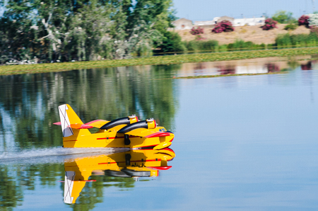 A floating Radio controlled model hydroplane speeds up to take off on Guadiana river.