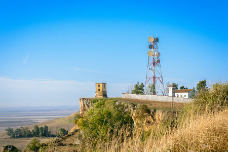 Telecommunication towers against blue sky and distant landscape with copy space for text Stock Photo