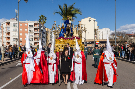 BADAJOZ, SPAIN - MARCH 26, 2018: Nazarenes and Jesus riding a donkey, during the celebration of Palm Sunday.