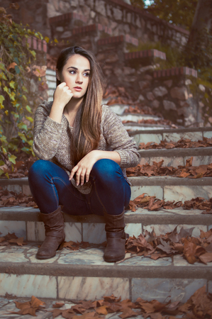 Young beautiful woman sitting on stairs in park Stock Photo
