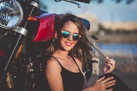 Young pretty  woman sitting on ground next to nake racer motorbike.
