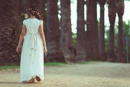 Beautiful girl in white dress walking in park
