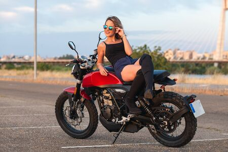 beautiful young woman lying on a motorcycle