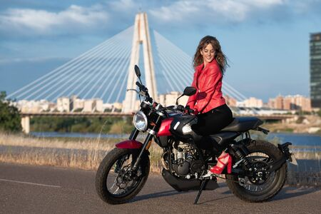 happy young woman sits on a red motorbike