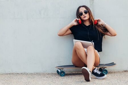 Young woman sitting on skateboard and holding tablet