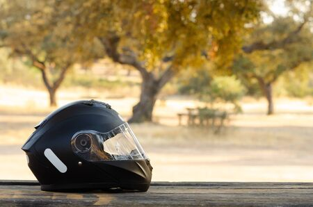 Biker helmet on wooden table with copy space for text Reklamní fotografie