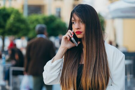 Portrait of Beautiful young woman using her cell phone on the street