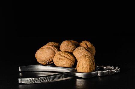 Walnuts with nutcracker over black background. Stockfoto