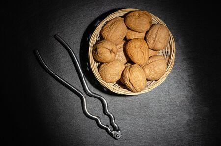 Walnuts with nutcracker on black background, top view. Stockfoto