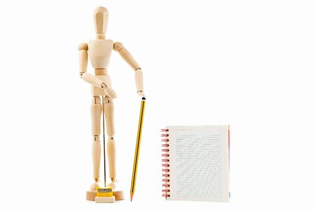 Wooden toy figure with pencil and notebook on white background