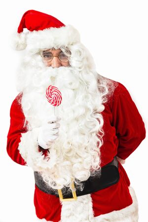 Portrait of  Santa Claus holding candy looking at camera on white background