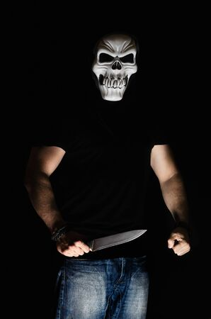 Man with scary mask and knife in halloween