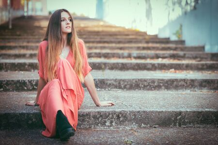 Beautiful gil sitting on outdoors stairs wearing red dress.