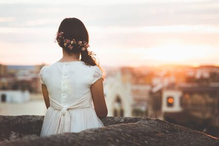 meisje in communie jurk kijken naar de stad bij zonsondergang Stockfoto