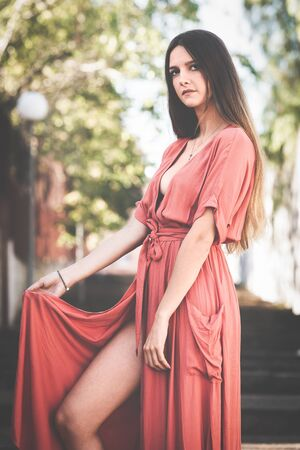 beautiful young woman with red dress posing in the street Stock Photo
