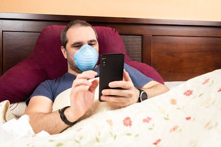 sick man laying in bed using smarthphone
