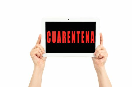 hands holding a tablet on a white background with quarantine text in spanish