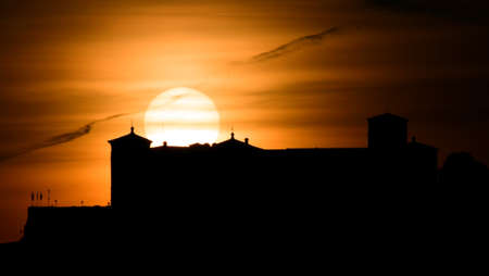 Big sun falling behind the silhouette of a castle moving on top of a mountain