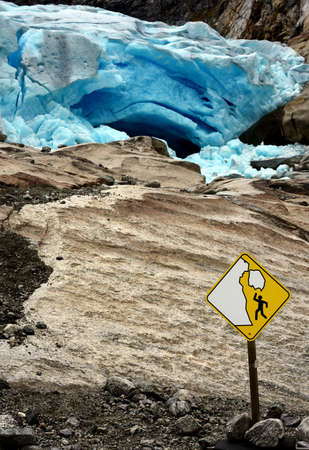 Yellow warning sign for collapse of Norwegian glacier with glacier in background