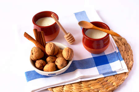 Natural goat milk curd with cinnamon, walnuts and honey in clay glass and wooden spoon