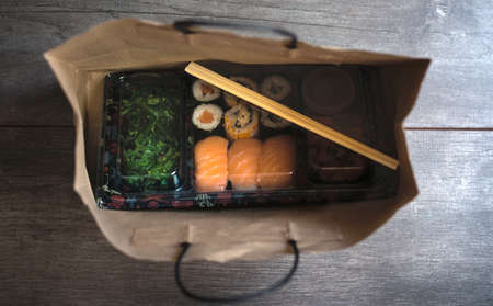 Sushi to go concept. Top view of takeaway box with sushi rolls and chopsticks in brown paper bag on wood floor. Maki. Sashimi. Salmon. Tuna. Wakame. Asian. Japanese. Paper bag.Take-away japanese food concept.