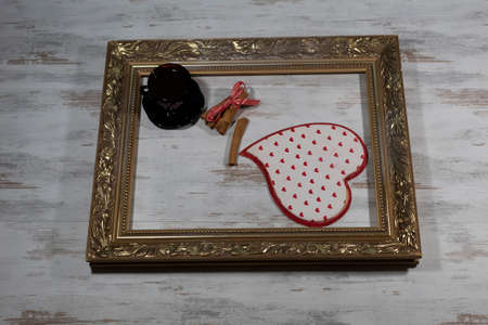 Festive background for Valentine's Day. In the old, gilded frame on a wooden background in the lower corner is a big heart. At the top is a cup of coffee and cinnamon sticks tied with a red ribbon.