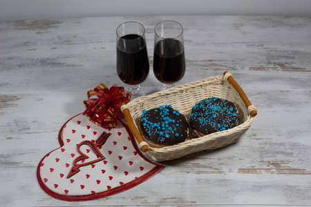 Two glasses of wine. Nearby is a big heart, a heart pierced by an arrow and a red bow. In a wicker basket, two delicious cakes.